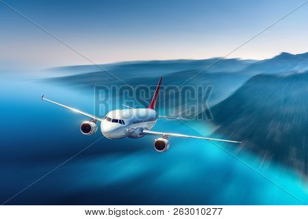 Airplane Is Flying Over Blue Sea And Mountains At Sunset. Landscape With Passenger Airplane, Island