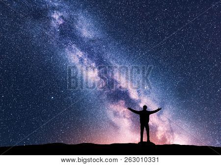 Milky Way And Silhouette Of A Standing Happy Man With Raised Up Arms. Travel In Nepal. Landscape Wit