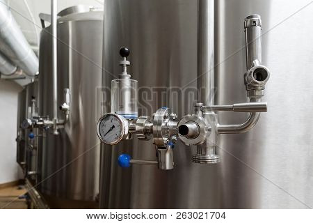 Craft beer brewing equipment in brewery. Metal tanks, alcoholic drink production. Facilities in modern interior of brewery. Manufacturable process of brewage. Mode of beer production. Brewing area poster