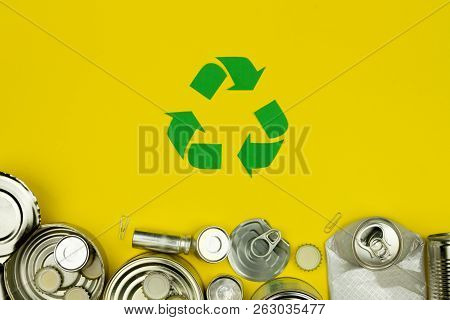 Green Recycle Reuse Sign Symbol With Metal Aluminium Cans, Covers, Jars On Yellow Background. Eco Ec