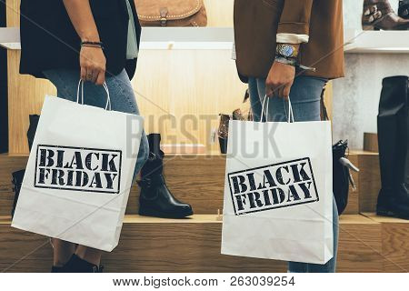 Black Friday. Cropped View Of A Couple Of Young Female Shoppers Holding Paper Shopping Bags In A Sho