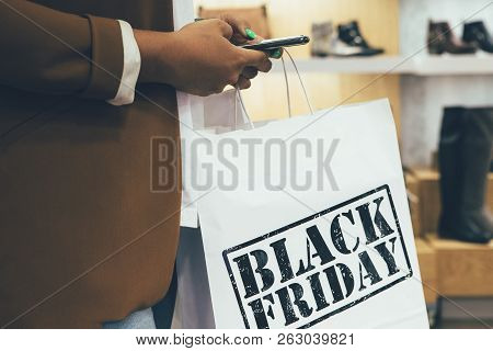 Black Friday. Close Up Of A Cropped View Of A Female Shopper Holding Paper Shopping Bags While Is Lo