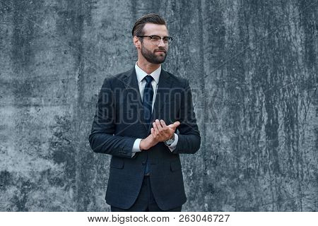 A Young Businessman With Glasses And A Beard Claps His Hands