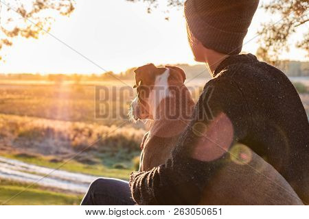 Hugging A Dog In Beautiful Nature At Sunset. Woman Facing Evening Sun Sits With Her Pet Next To Her