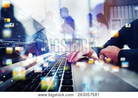 Business People Work Together In Office With Laptop In The Foreground. Concept Of Teamwork And Partn