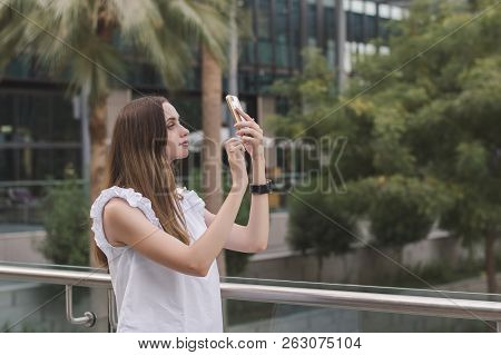 Young European Female With Brown Hair And In White Casual Style Blouse Taking Photos With Her Mobile
