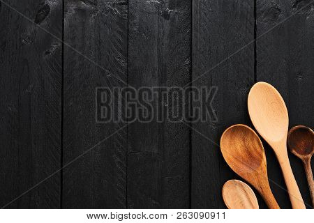 Wooden Spoons On Black Wooden Background With Copy Space. Top View Of Various Types Of Wooden Spoons