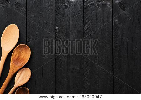 Wooden Spoons On Black Wooden Background With Copy Space. A Collection Of Wooden Kitchen Utensils On