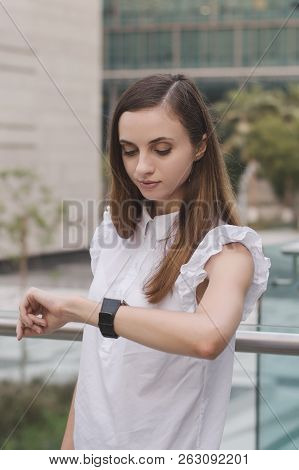 Vertical Photo Of Young European Business Woman Looking At Her Hand Watches. Time Management. Deadli