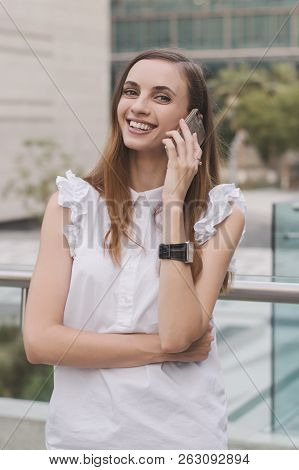 Young European Female Talking Via A Mobile Phone With Happy And Smiling Face. Successful Office Work