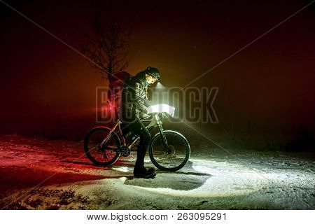 Extreme Winter Mtb Race. Cyclist Man With Winter Bike Stays In Snow And Check The Paper Map Under He