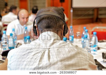 Unrecognizable People Using In Ear Headphones For Translation During Event Unrecognizable Business P
