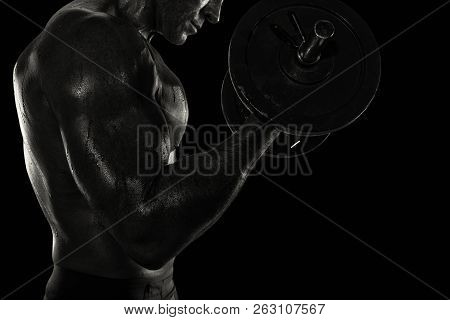 Athletic Man Training Biceps At The Gym. Black And White Effect