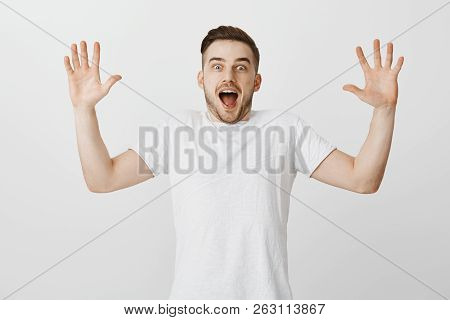 Studio shot of excited enthusiastic handsome male with bristle raising palms hight and shouting from happiness and amazement being surprised with awesome news reacting to fascinating story poster