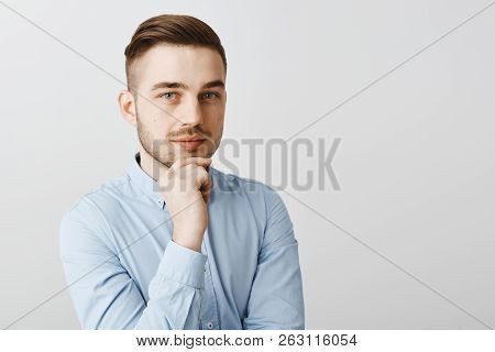 Waist-up Shot Of Smart Creative Male Boss In Formal Blue Shirt Being Ambitious And Optimistic Holdin