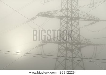A Tower Supporting A High-voltage Electrical Line In Dense Fog. Through The Fog Visible Solar Circle