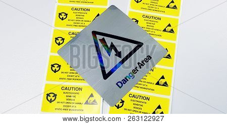 Danger Signs And Yellow Caution Label On Table. Dangerous Area Within Industrial Area.