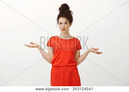 Portrait Of Indifferent Careless Caucasian Curly-haired Woman In Red Dress, Shrugging With Spread Ha