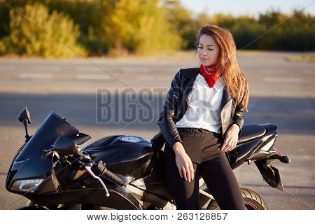 Horizontal View Of Thoughtful Biker Stands Near Favourite Motorbike, Dressed In Stylish Outfit, Has