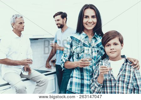 Smiling Family Drinking Water In Glasses At Home. Father And Son. Smiling People. Parenthood Concept