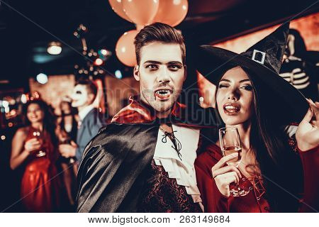Young Happy Couple In Costumes At Halloween Party. Handsome Man And Beautiful Woman Drinking Champag