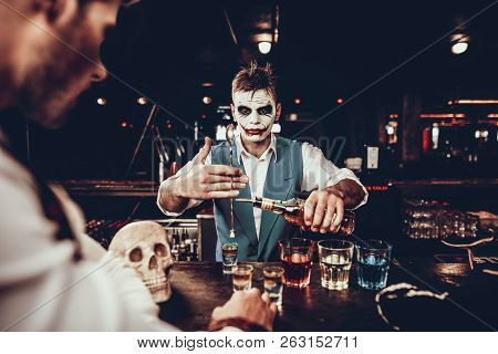Bartender In Halloween Costume Making Cocktail. Portrait Of Young Man Wearing Costume Standing At Ba
