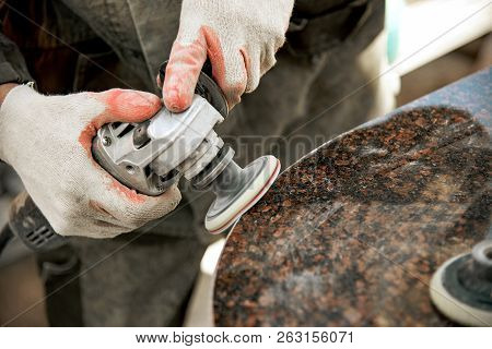 Worker In Gloves Polishes A Marble Stone With An Angle Grinder
