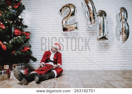 Drunk Santa Claus Near New Year Tree After Party. Christmas Tree In Office. Celebrating Of New Year.
