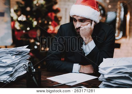 Tired Man Working With Documents On New Year Eve. Christmas Tree In Office. Business Concept. Man In