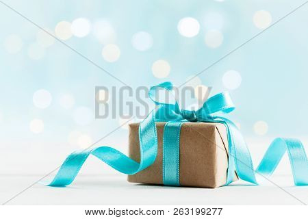 Christmas Gift Or Present Box Against Turquoise Bokeh Background. Holiday Greeting Card.