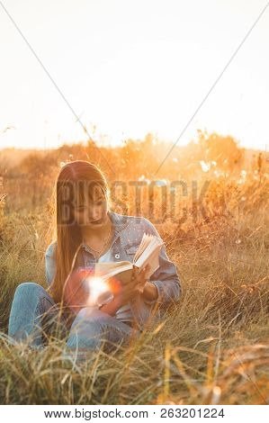 Beautiful Girl In Autumn Field Reading A Book. The Girl Sitting On A Grass, Reading A Book. Rest And