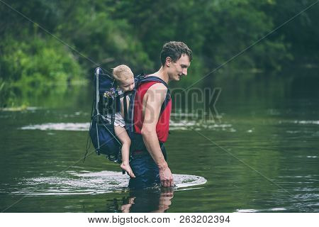 A Man With A Child Crosses The River. The Father Carries The Son In A Backpack. Rescue From Flooding