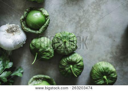 Garlic and green tomatillos on a gray table