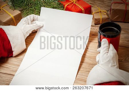 Santa Claus Holding Letter On Wooden Table With Gift Boxes And Christmas Tree And Cup Of Hot Coffee