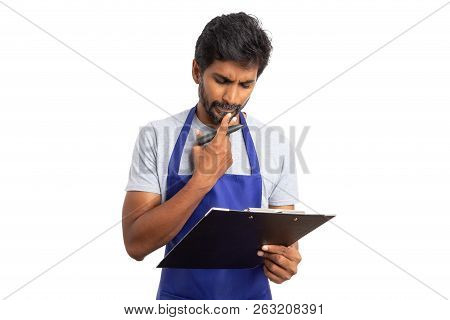 Indian Man Store Owner Or Supermarket Employee Thinking As Looking At Supply List On Clipboard Isola