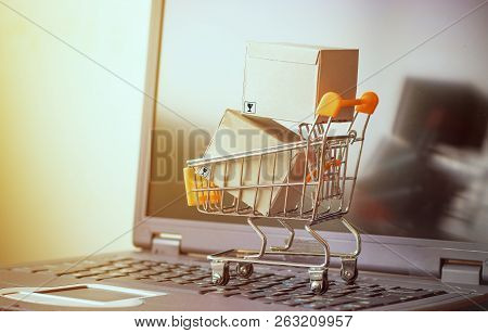 Cardboard Boxes Are In Trolley On Laptop. Idea For Online Shopping And E-commerce, Consumers Can Buy