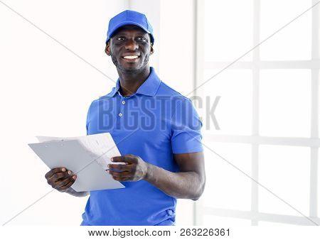 Portrait Of An Handsome Happy Deliverer With Folder