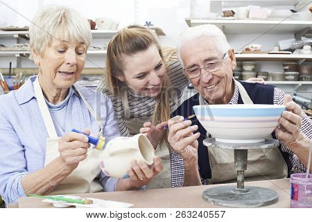Senior Couple With Teacher In Pottery Class