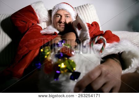Sexy, Naked Santa With Jacket And Hat Holding Candy Filled Stocking In Front Of Him