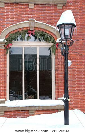 A classically styled exterior electric outdoor light in front of a brick building at Christmas.