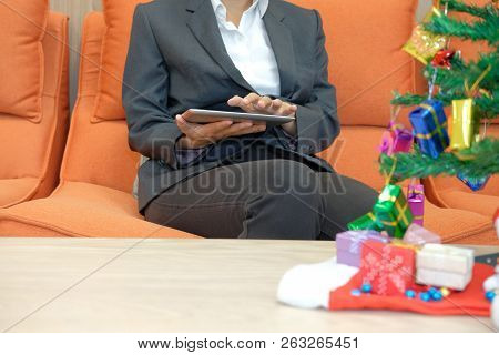 Woman Sitting On Sofa Using Tablet. Businesswoman Texting Message On Touchpad During Xmas. Christmas