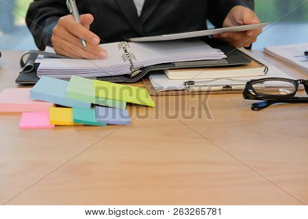Man Organizing Plan With Notebook & Tablet. Businessman Working  At Workplace Coworking Office
