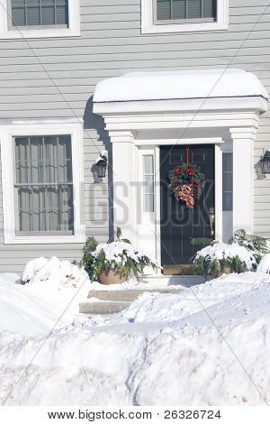 The front door of a snow covered home decorated with a Christmas wreath.