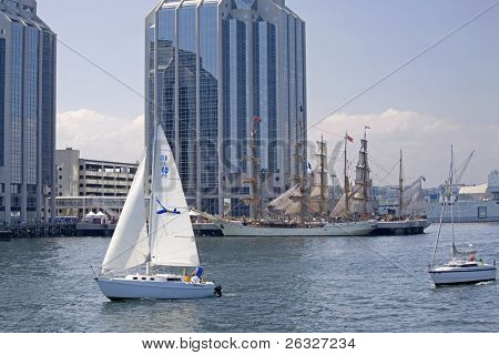 HALIFAX, NOVA SCOTIA - JUNE 20: Sailboats sail along the Halifax waterfront the Nova Scotia Tall Ships Festival 2009. In the background are the Europa and the Picton Castle tied up at Purdy's Wharf on June 20, 2009 in Halifax, Nova Scotia.