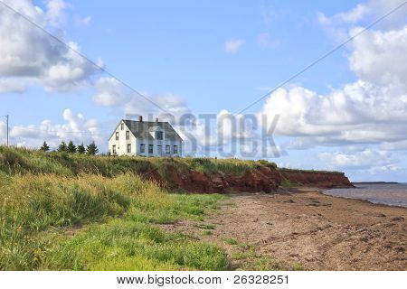 An old wooden house alone on a shoreline cliff in rural Prince Edward Island, Canada.