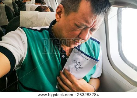 Suffering Asian Man Holding Air Sickness Vomit Bag In Airplane