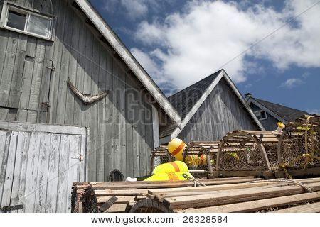 Bait sheds on a wharf in Prince Edward Island, Canada. Lobster traps and buoys are stacked in front.  A tail of a tuna hangs on the shed wall above the door.