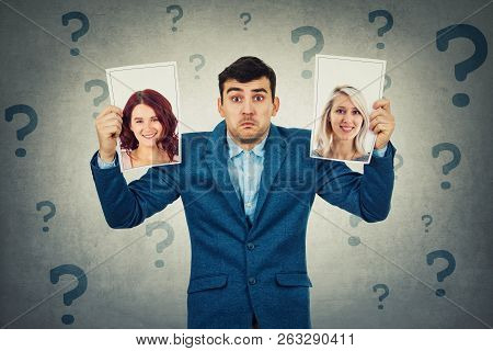 Undecided Young Man Holding Two Photos Has To Choose Between Two Woman, Question Marks Around Head.