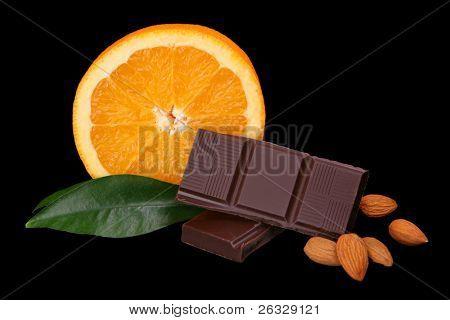 Chocolate, orange, hazelnuts and almonds on the black background.