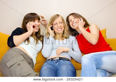Three young woman talking on phones while sitting on the sofa